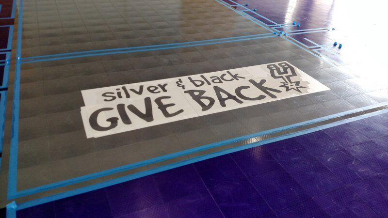 Silver and Black Give Back Logo on the Gym Floor at the Children's Shelter